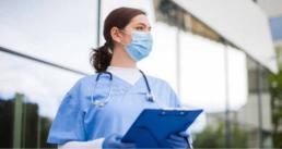 masked female medical worker holding clipboard