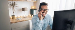 smiling man on phone looking at computer